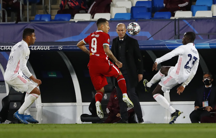 Liverpool's Roberto Firmino in action with Real Madrid's Ferland Mendy as Real Madrid coach Zinedine Zidane looks on