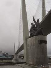 Photo: Revolutionary monument and suspension bridge in the morning fog