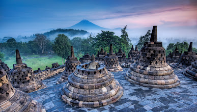 Photo: The Hidden Buddhist Temple of Borobudur at Sunrise  This morning I got a wakeup call at 3:30 AM to head out on a distant trek to Borobudur to climb the temple before sunrise.  I had a flashlight and a fully loaded iPod for the ascent.  I stayed at the top and all around the temple for most of the morning, collecting shots here and there as misty clouds rolled in, through, around, and over the temple.  This temple laid abandoned and overgrown for about 800 years until it was rediscovered by the British.  You can see the distant volcano rumbling in the morning sunrise...  from the blog at www.stuckincustoms.com