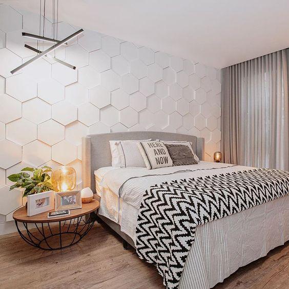 Quarto de casal com revestimento hexagonal branco em 3D na parede de fundo, piso de madeira e mesinha de canto de madeira com estrutura de ferro preto
