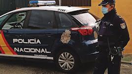 Imagen de archivo de un coche y una agente de Policía Nacional.