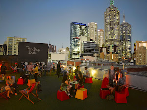 People enjoy drinks at the Rooftop Bar & Cinema at Curtin House at twilight in Melbourne.