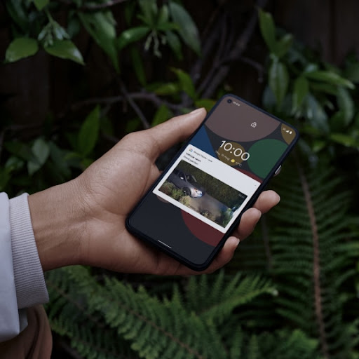 A person holds their phone in their hand and checks in on their home while they're out.
