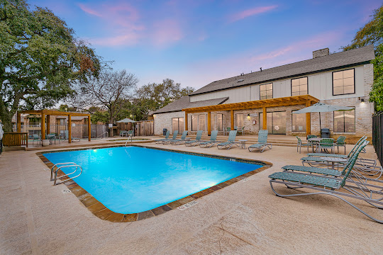 Connemara Estates apartment swimming pool with lounge chairs just outside community clubhouse at dusk