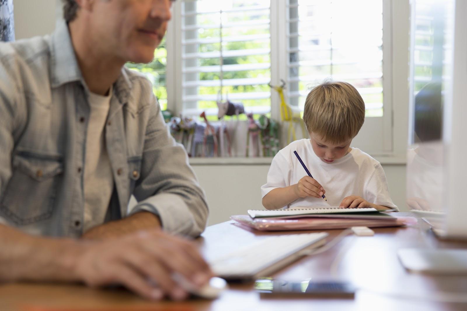 Foto de um pai e um filho sentados em uma mesa, enquanto o pai realiza suas atividades de teletrabalho, a criança realiza suas atividades escolares.