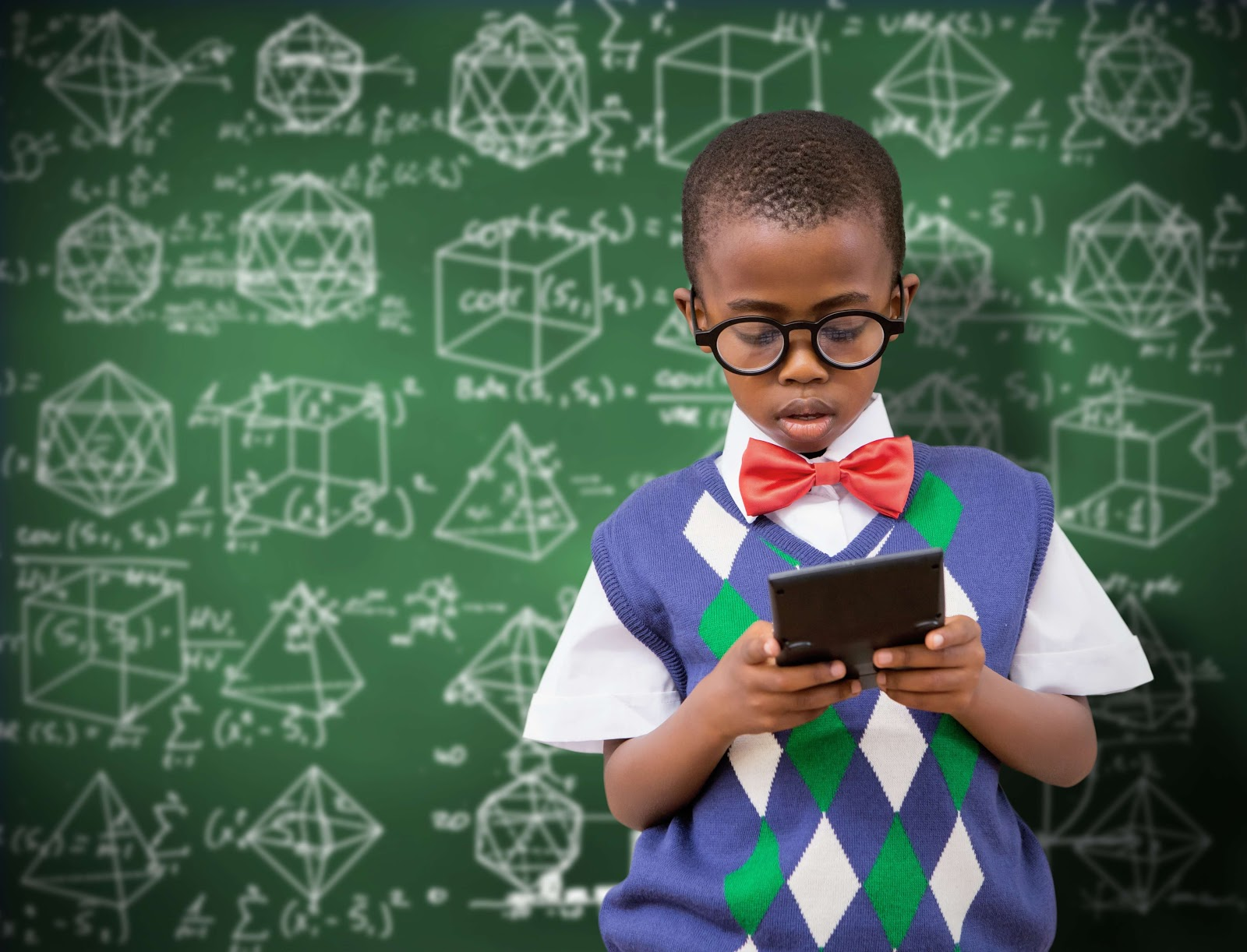 A kid holding a calculator in front of a blackboard