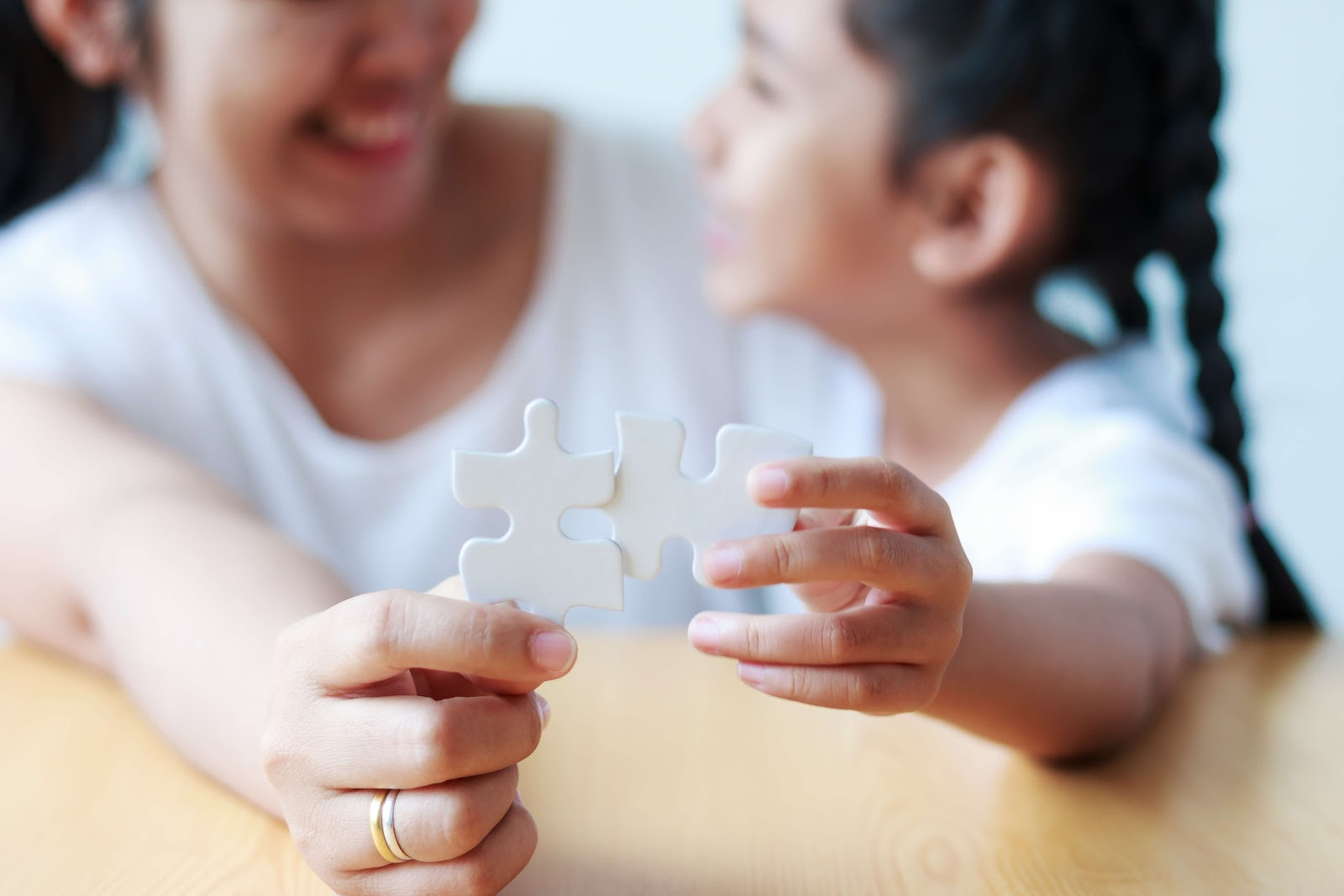 A parent and child holding two puzzle pieces that don't fit together