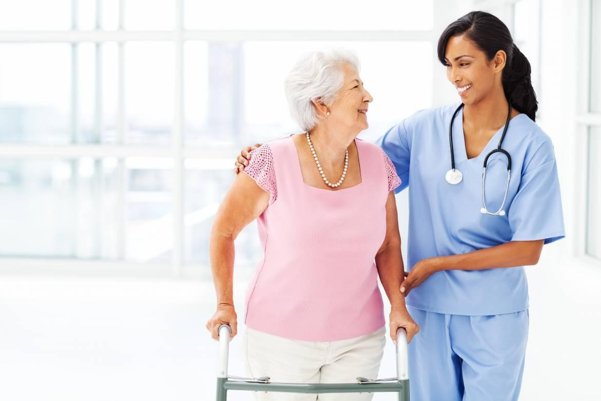 Nurse Assisting Elderly Woman With Walker While Looking At Her - Safe Care  Home Support