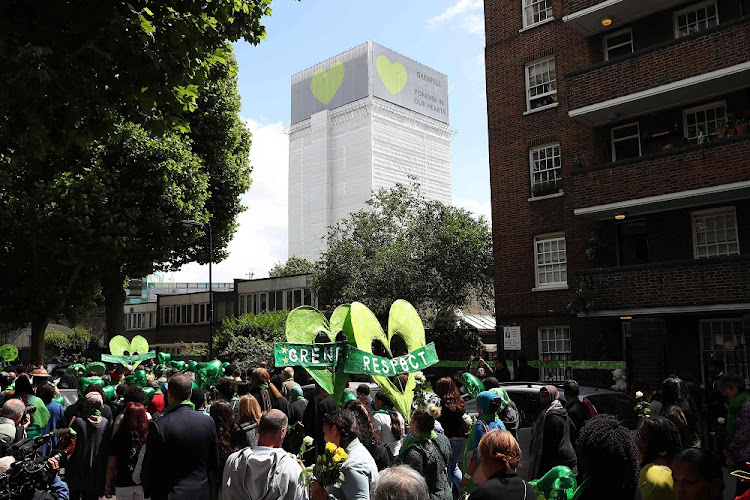 Remembering Grenfell: Members of the public hold banners as they take part in a procession to Grenfell Tower as part of commemorations on the anniversary of the Grenfell fire in west London. Picture: REUTERS
