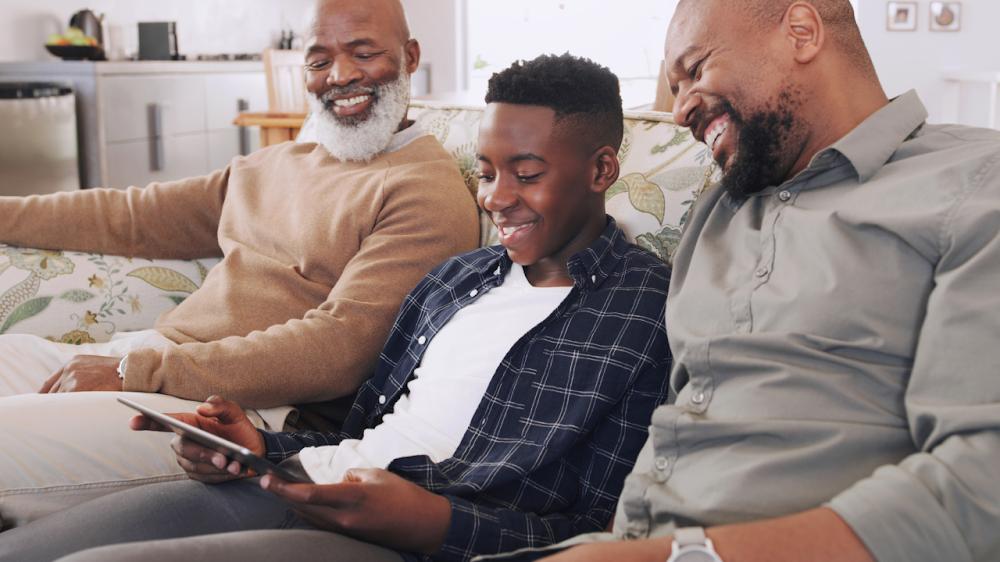 Dos hombres mayores y un niño mirando un tablet