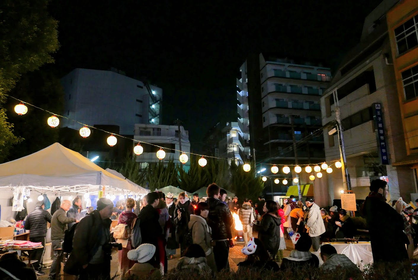 Even at 8 PM on NYE, there are already plenty of people gathered around the bonfire at Oji Inari-Jinja Shrine where there is sake and snacks too. Lots of fox masks! This is the endpoint for the Oji Kitsune-no-gyorestu Fox Parade.