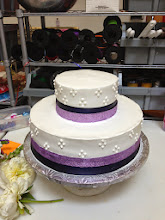Photo: Floral Wedding Cake (before flowers): 2-tiers frosted in white, Italian whipped cream. Decor: smooth sides with 4-dot  cluster in white and double ribbon wrap around bottom with plum, satin ribbon (below) and lavender, glitter ribbon (above).