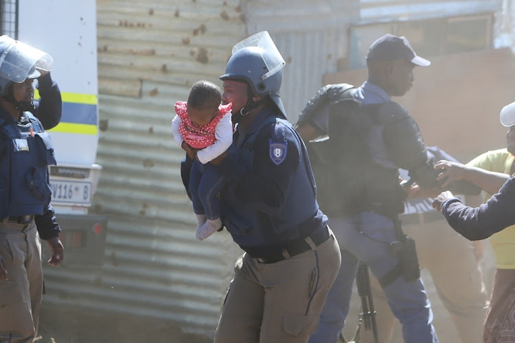 A Nelson Mandela Bay metro police officer takes the child to safety after her father threw her off the roof of a shack at the Joe Slovo informal settlement in Port Elizabeth on 12 April 2018.