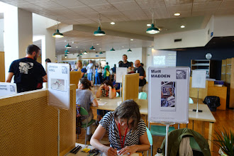 Photo: View of the third floor of the library that hosts the festival. Carrels turned into dédicace stations.