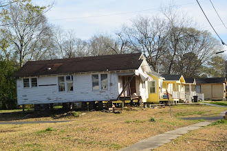 Photo: 21Feb14MostlyDelphine.  General view of the 4-room house raised for leveling, I think.  I count the high windows at left as a bathroom; if a kitchen it will count as more than 4 rooms.  If a duplex, ....