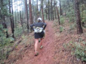 Photo: Deb powering up a slick muddy trail