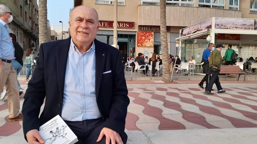 """Antonio Torres, doctor en Periodismo, con un ejemplar de """"¡Llévame contigo...! en el Paseo Marítimo."""