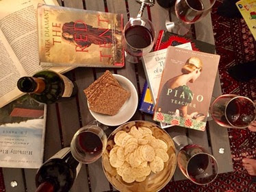Coffee table with books, snacks, and wine glasses