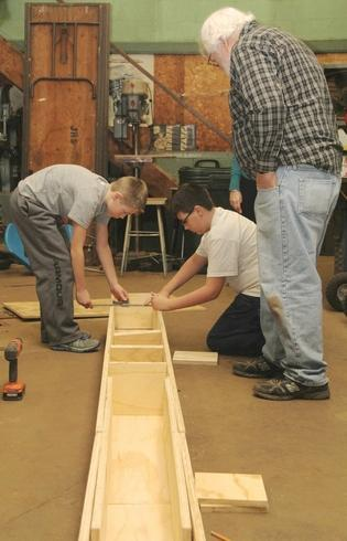 Ray Leising watches as sixth-graders Kaden Playford and Dorian Fonke work on a template to build a canoe.