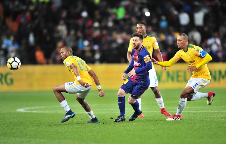 FC Barcelona captain Lionel Messi glides past Tiyani Mabunda (L), Sibusiso Vilakazi (C) and Wayne Arendse of Mamelodi Sundowns during the Nelson Mandela Centenary Cup match at FNB Stadium in Soweto, Johannesburg, on Wednesday May 16 2018.