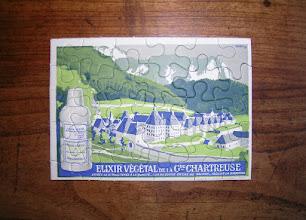 """Photo: Parviendrez-vous à assembler les pièces de ce puzzle publicitaire au format carte postale ? L'illustration ainsi reconstituée laisse apparaître le monastère de la Grande Chartreuse et un flacon à double-étiquette caractéristique de l'entre-deux-guerres... Élixir végétal, """"exigez-le si vous tenez à la qualité"""" !"""