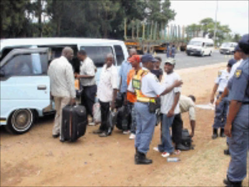 CRACKDOWN: Police at the roadblock on the N4 highway in Malelane near the Mozambique border search taxi passengers.  15/01/2009. Pic. Riot Hlatshwayo.  © Sowetan.