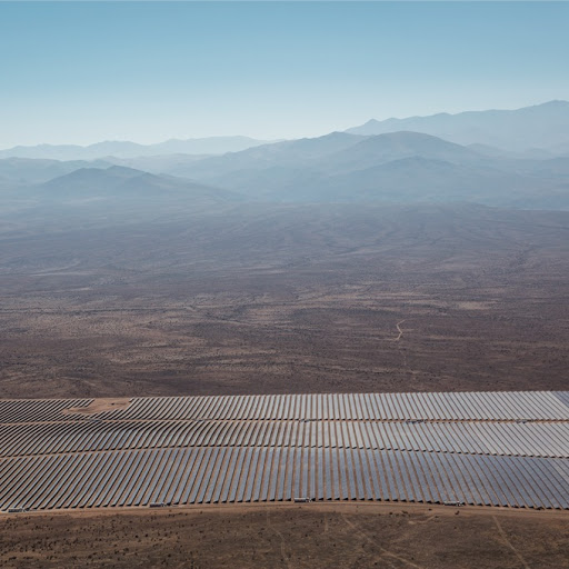 Solar panel farm in the desert framed against a background of mountains