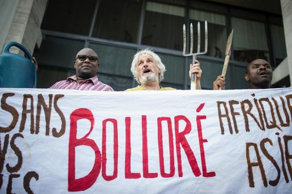Protesters demonstrate in front of Bolloré's headquarters near Paris calling on the multinational conglomerate to return land, or compensate farmers, over disputed concessions for plantations in Cambodia and three African countries yesterday. Bollore is the largest shareholder of Socfin, which has been accused by activists of land grabs in Cambodia, Liberia, Cameroon and Ivory Coast. Photo: Kamil Zihnioglu/AP
