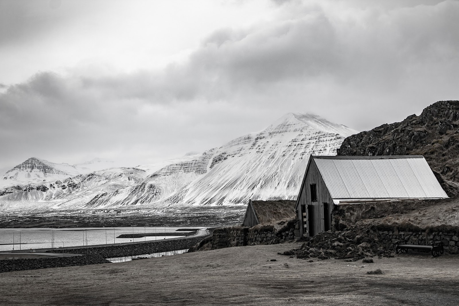 small garage metal and wooden shed on the shore of water and snow covered mountains in background on a cloudy day in akureyri iceland black and white