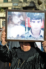 Photo: This woman attends nearly every protest carrying this photo of her son, tortured and killed by the army, she said, for refusing to carry out order to use violence against protesters.