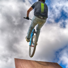 Off The Ramp by Marco Bertamé - Sports & Fitness Other Sports ( clouds, wood, speed, letter, green, a, dow, helmet, stunt, take-off, bicycle, jump, flying, red, sky, eamp, blue, cloudy, brown, grey )