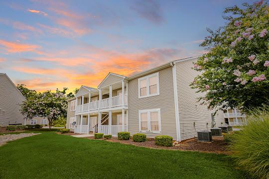 Winter Ridge & Montclair apartment building with light brown siding at dusk