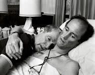 zieke man in bed omhelst zijn naast hem liggende broer