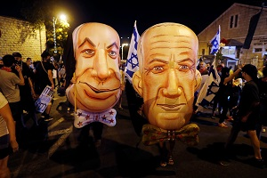 Demonstrators wear masks depicting Israeli Prime Minister Benjamin Netanyahu and Israel's Alternate Prime Minister and Defence Minister Benny Gantz during a protest against Israeli Prime Minister Benjamin Netanyahu's alleged corruption and economic hardship stemming from lockdown during the coronavirus disease (Covid-19) crisis, near his residence in Jerusalem August 8, 2020.