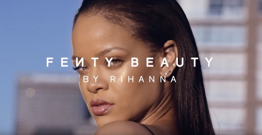 A frame from the video showing Rihanna looking over her shoulder with the Fenty Beauty by Rihanna logo over her face.