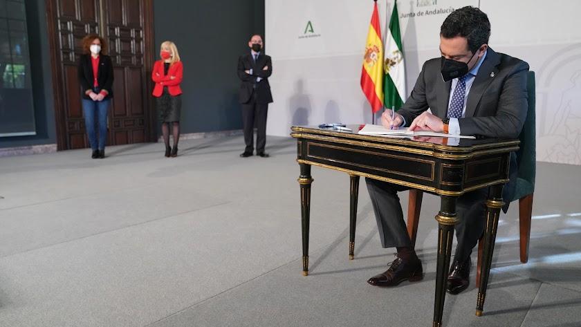 Juanma Moreno firma el acuerdo.