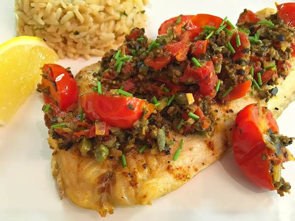 Grilled Fish Topped With Tapenade On A White Plate Along With Lemon Wedge And Rice.