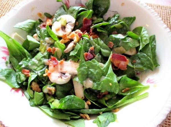 Now, pour the hot dressing over the spinach - tossing to coat well. Sprinkle...