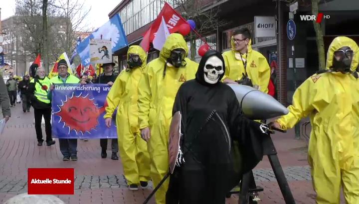 Als Strahlenschützer und Tod verkleidete Ostermarschierer:innen mit Bombenattrappe.