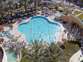 Photo: A view of the main outdoor pool from the room.  The smaller pool to the left is filled with Dead Sea water as is another pool inside the spa further to the left.