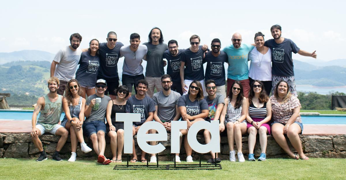 Grupo de pessoas posando para foto junto a uma placa com o logo da Tera.