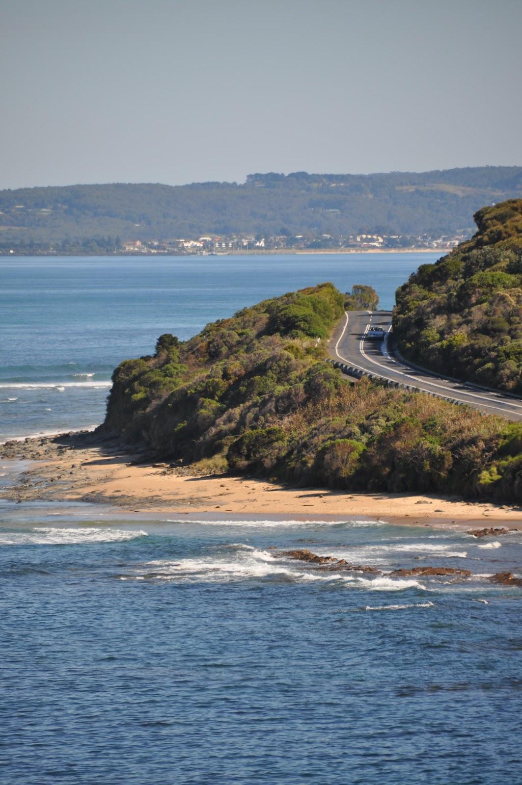 car on scenic coastal road near beach and blue ocean in australia great ocean road apollo bay in background. See the scenic great ocean road during our australia road trip itinerary.