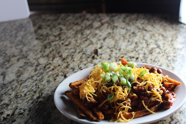 Put fries on a serving platter. Spoon chili over fries. Sprinkle with cheese &...
