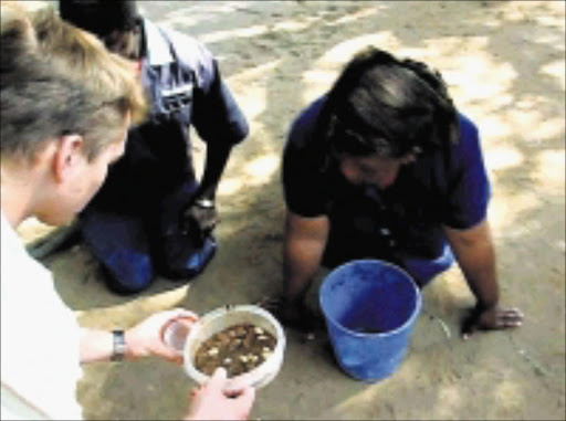 HUMILIATION: A photo from a DVD made by students showing Free State University cleaners eating meat that had allegedly been urinated on as part of a mock initiation. It is believed the DVD was made to protest against the racial integration of the hostels.