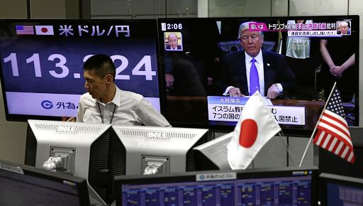 Trumpeting the noise: An employee of a foreign exchange trading company stands in front of a TV monitor showing US President Donald Trump and another monitor showing the Japanese yen's exchange rate against the US dollar in Tokyo. Picture: REUTERS