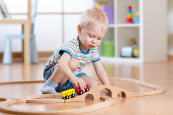 Little boy playing with his train set