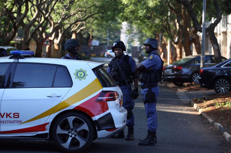 Hawks and members of the SAPS are seen outside the Gupta compound in Saxonwold, Johannesburg on 14 February 2018.