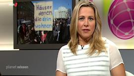 Bild aus Video: Moderatorin im Studio, Hintergrund: Demo, Transparent: «Häuser denen, die drin wohnen».