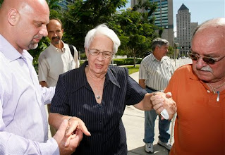 Photo: Mirta Rodriguez, center, mother of convicted Cuban spy Antonio Guerrero, assisted by unidentified supporters as she leaves federal court in Miami, Tuesday, Oct. 13, 2009. Guerrero has received a reduced prison sentence of nearly 22 years after his original life term was tossed out by an appeals court. A federal judge in Miami imposed the new sentence Tuesday on 50-year-old Antonio Guerrero. It is nearly two years longer than an agreement reached by prosecutors and defense lawyers. (AP Photo/Alan Diaz)
