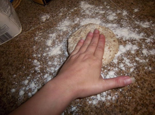 Use your hand to slightly flatten the dough ball, then start rolling.